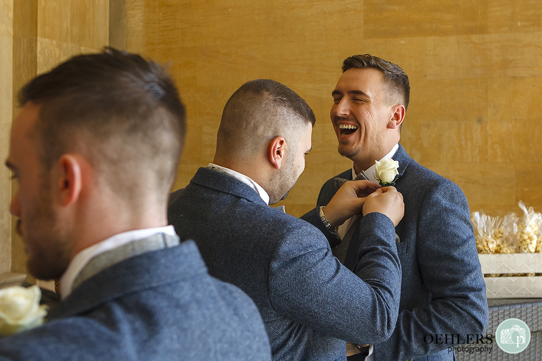 Groom laughing as a groomsman pins his buttonhole.