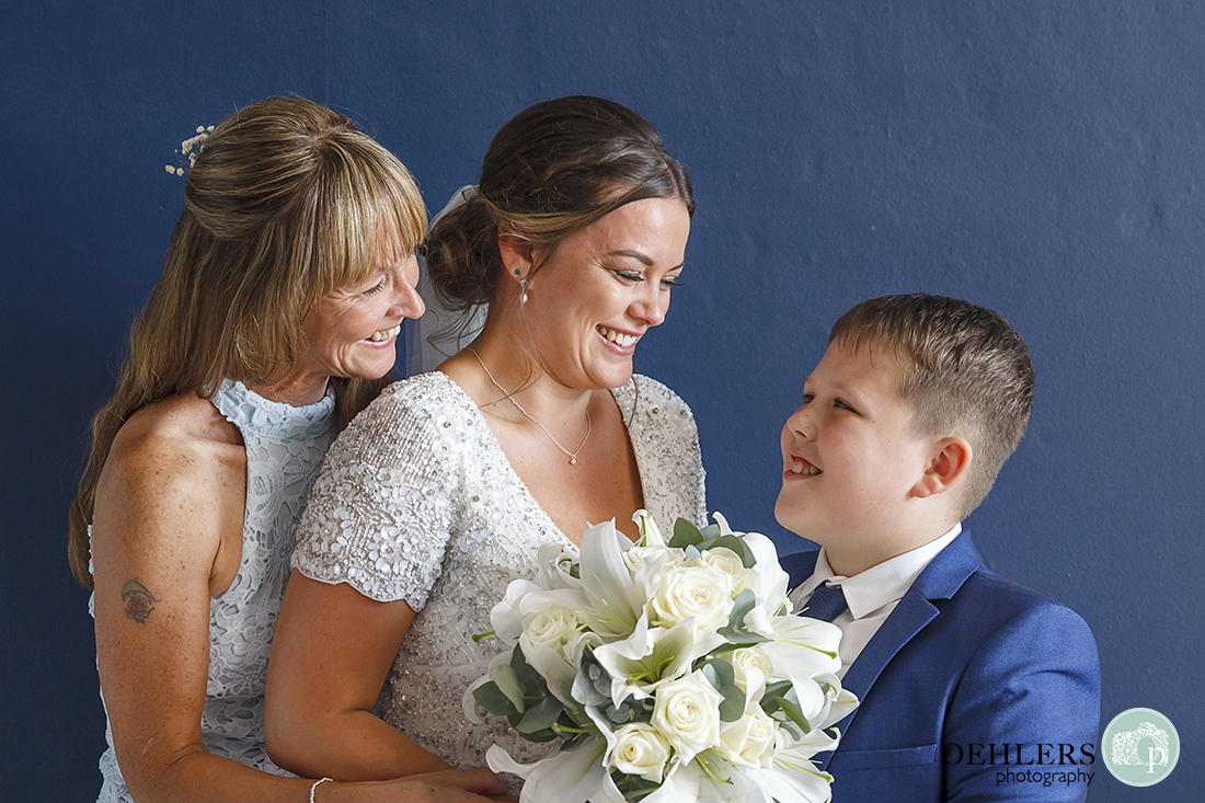 Bride with her mum hugging her and her little brother looking at her.