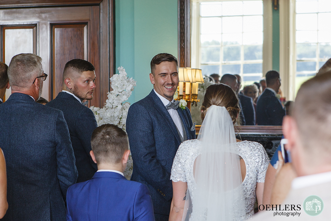 Wedding photographer at Prestwold - Groom smiling looking at his bride walking down the aisle.