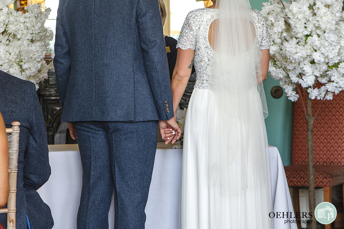 Wedding photographer at Prestwold - Close up of Bride and Groom holding hands at the ceremony table.