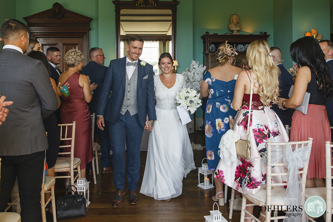 Wedding photographer at Prestwold - Both groom and bride walking back up the aisle with beaming smiles.
