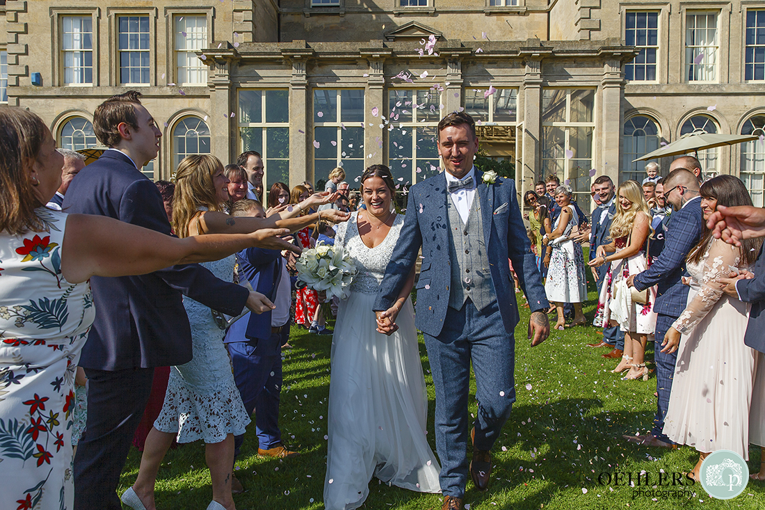 Wedding photographer at Prestwold - Confetti shot with happy guests and happy bride and groom.