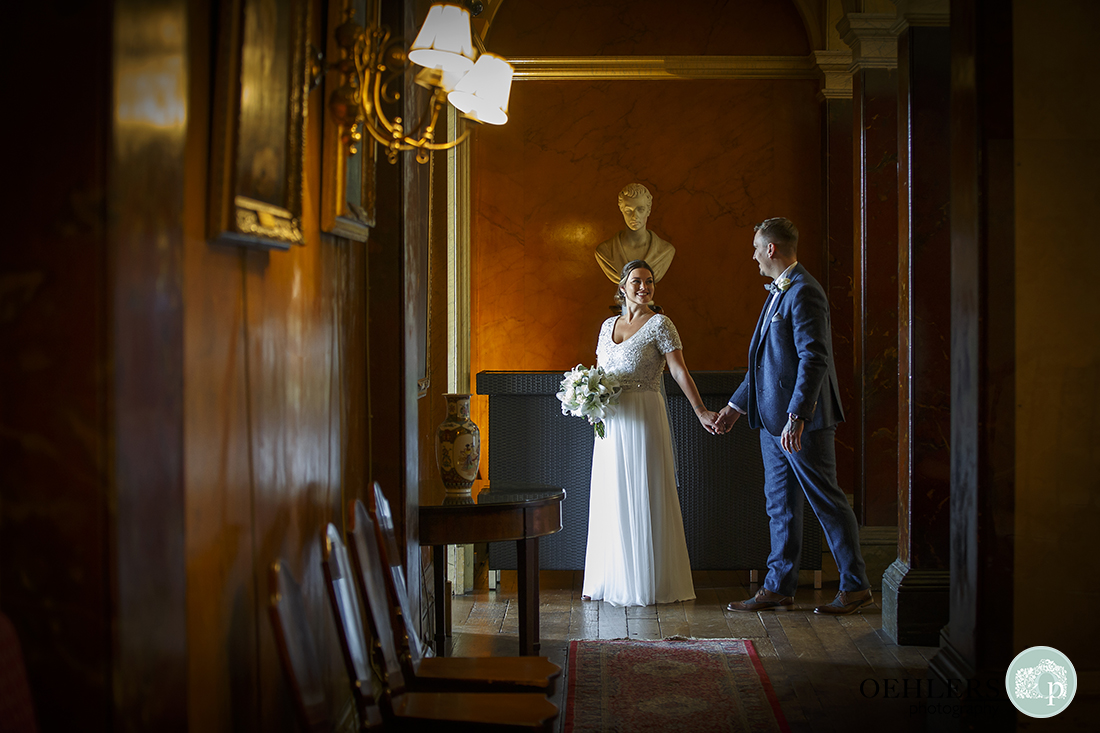 Wedding photographer at Prestwold - Lovely indoor image of bride holding hands with groom and leading him into a room.