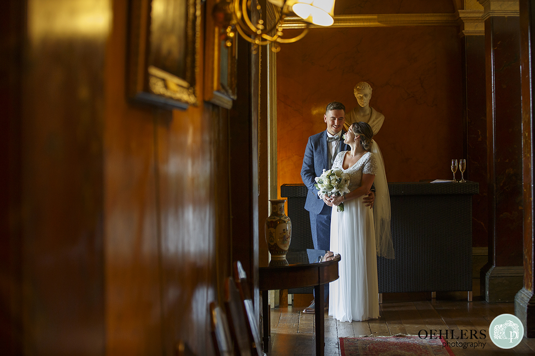 Wedding photographer at Prestwold - Lovely portrait of Bride and Groom looking at each other standing in a doorway.