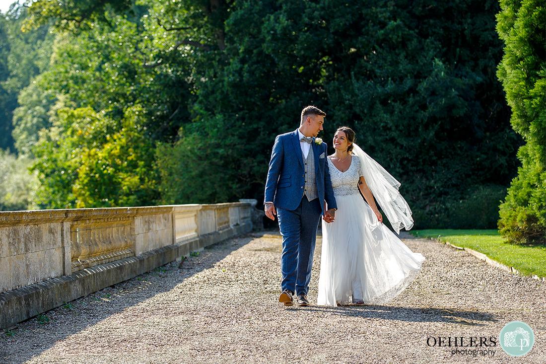 Wedding photographs in the garden - Bride and Groom strolling in Prestwold's garden bath in sunshine.