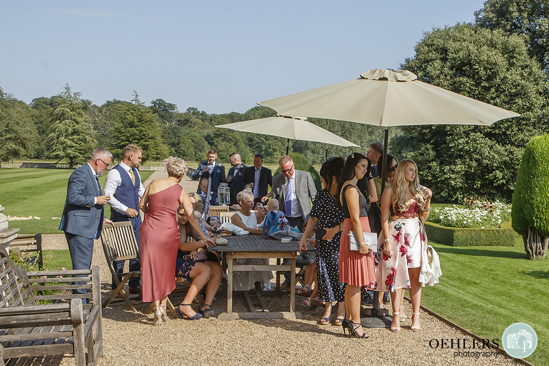 Prestwold Hall Wedding Photographs - Guests enjoying the sunshine in the garden of Prestwold Hall