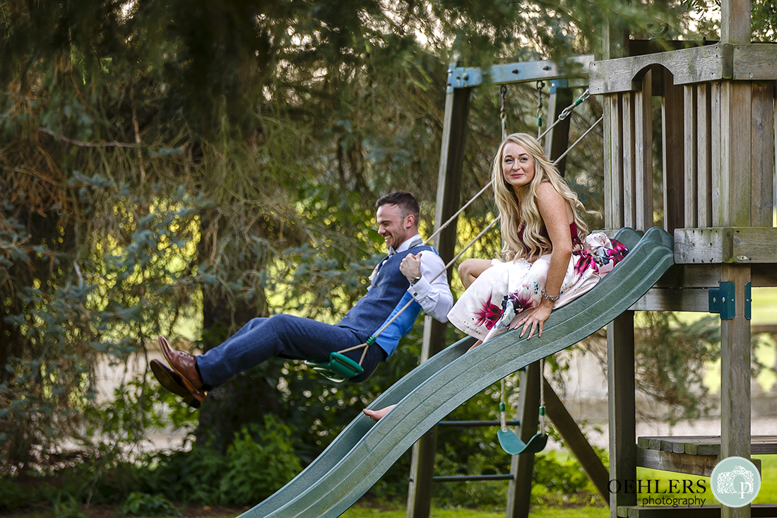 Prestwold Hall Wedding Photographs - Two guests going back to their youth on the swings and slide.