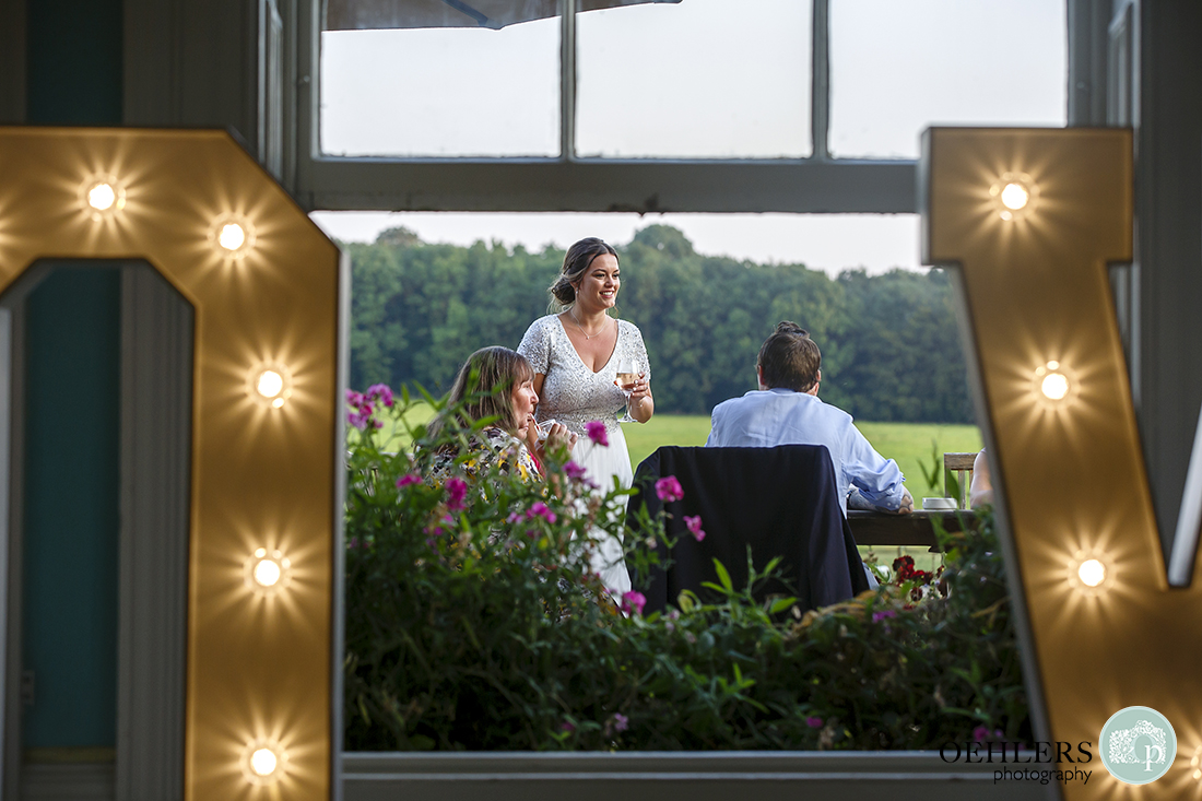 Prestwold Hall Wedding Photographs - Lovely photograph of the bride outdoors in between a Love sign.