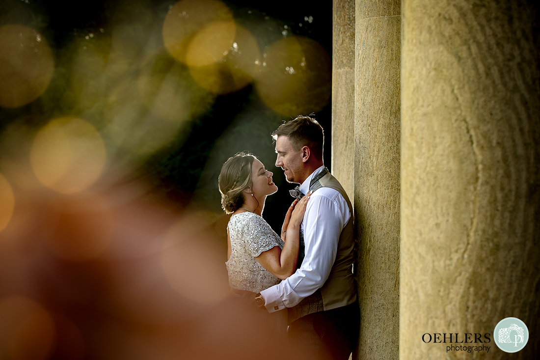 Prestwold Hall Wedding Photographs - A romantic image of the bride and groom shot through some lights.