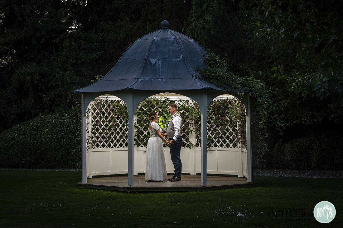Prestwold Hall Wedding Photographs - Night shot of the couple backlit in the outdoor gazebo.
