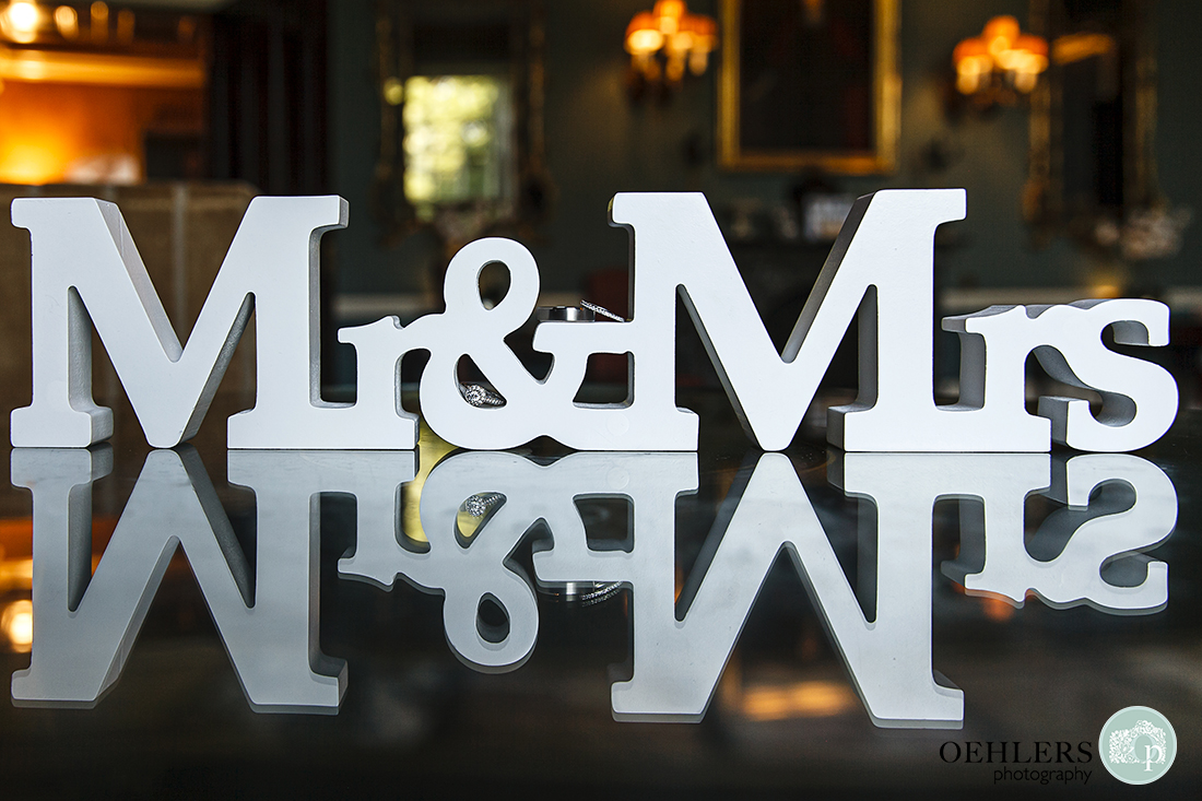 Prestwold Hall Wedding Photographs - Mr and Mrs Wooden Sign with the wedding rings balanced on it.
