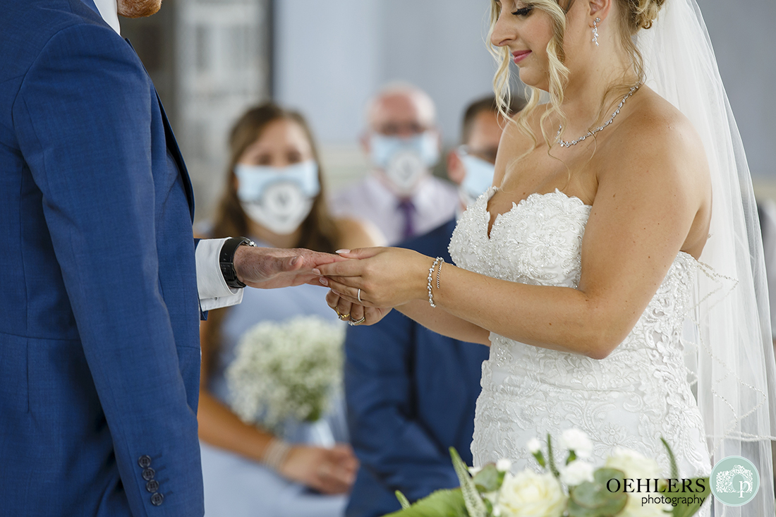 bride placing groom's wedding ring on his finger