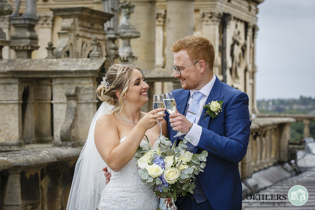 bride and groom toasting their marriage with a glass of champagne