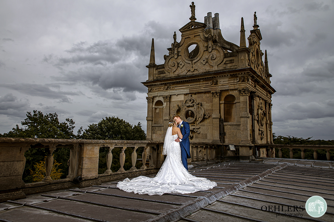 stunning photo of bride and groom on the rooftop of wollaton hall