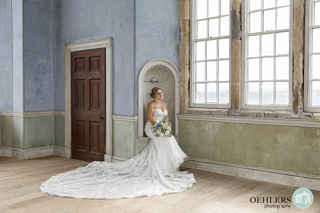wollaton hall wedding photography of the bride sitting in the prospect room