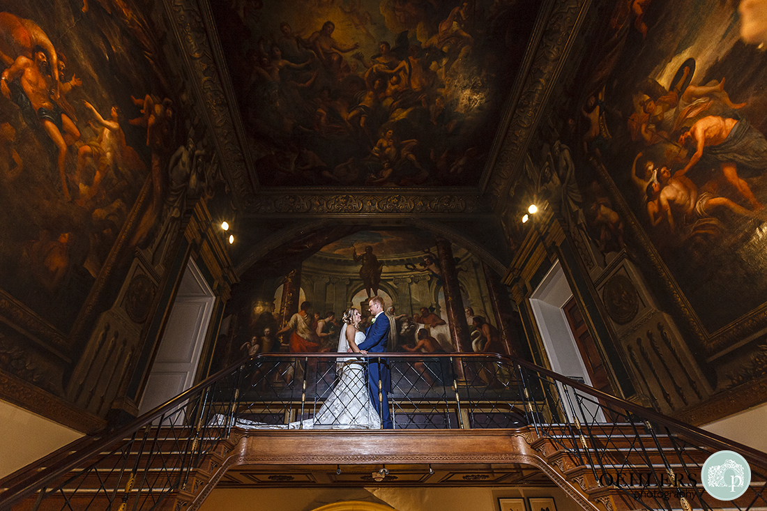 bride and groom standing on the landing surrounded by beautiful paintings on the walls