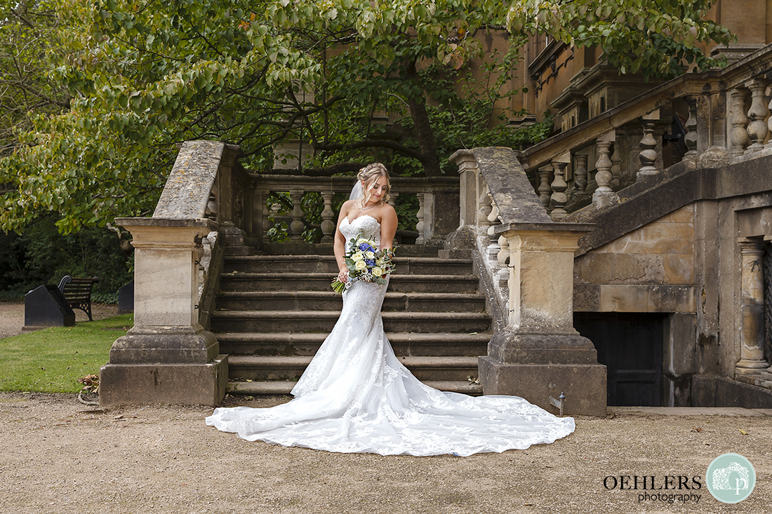 Beautiful bride posing at the bottom of an outdoor staircase at wollaton hall