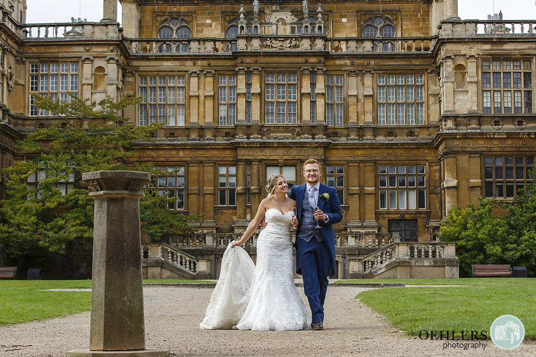 bride and groom with the majestic fascade of wollaton hall in the background