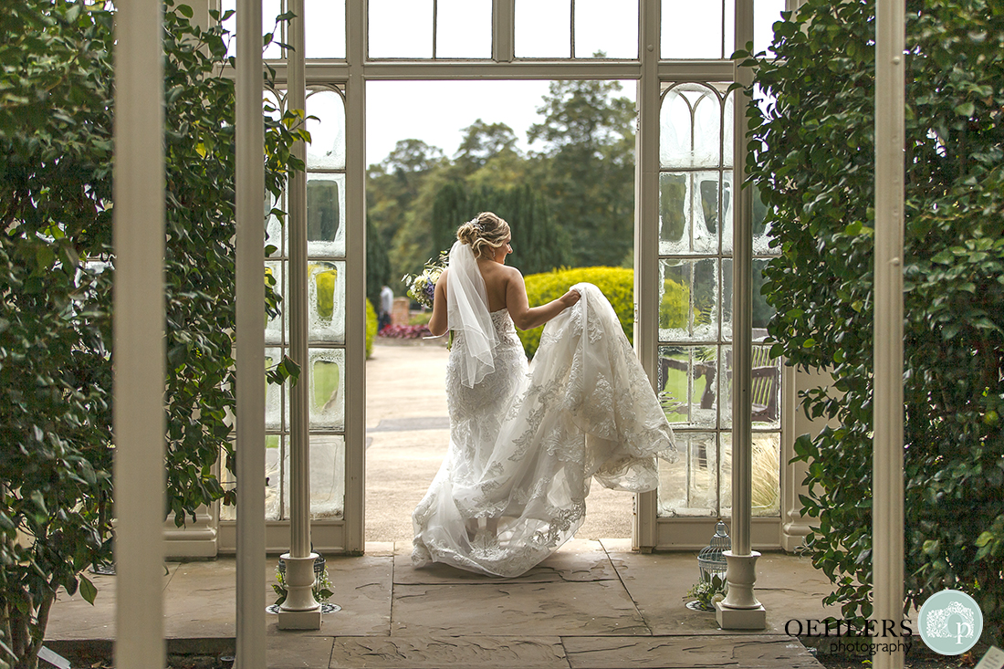 bride exiting the Camellia House holding her dress