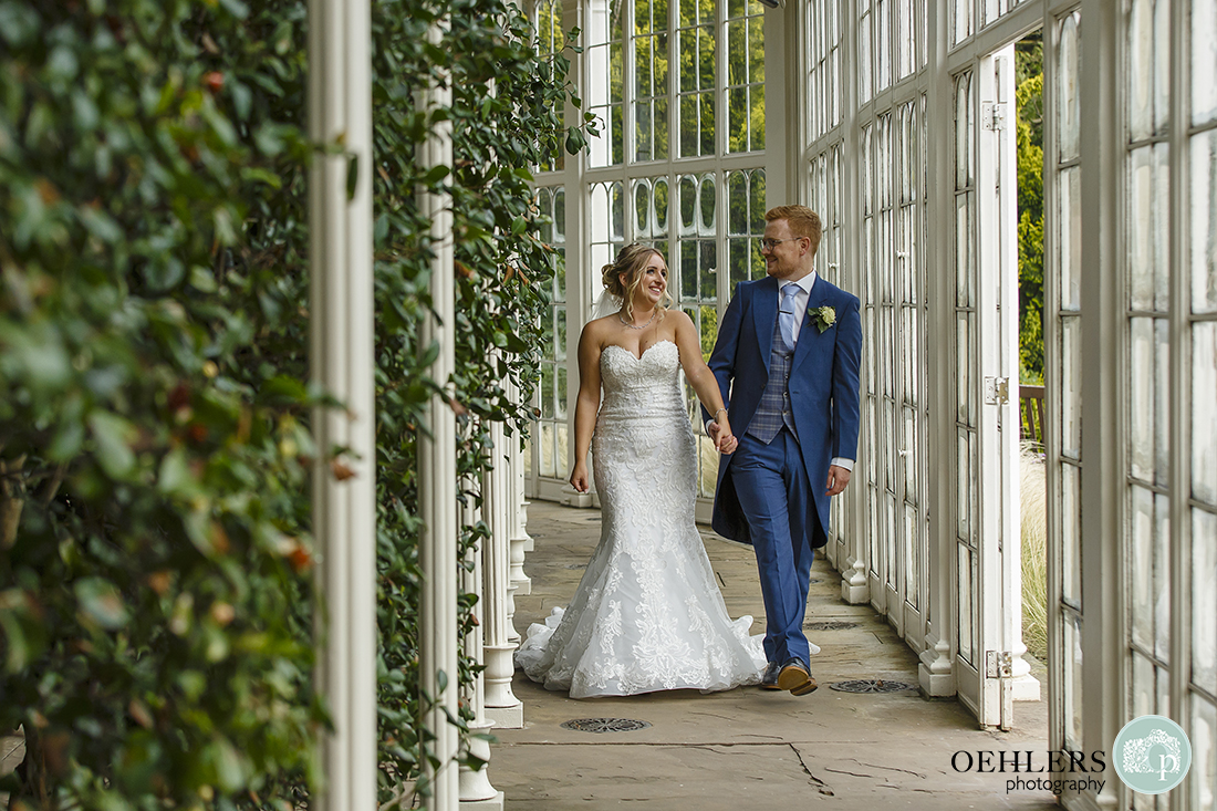 bride and groom walking in the Camellia House