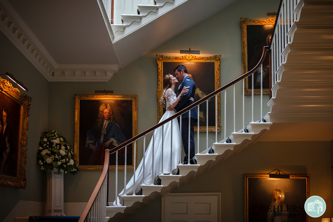 norwood park wedding photography - bride and groom kissing on the staircase