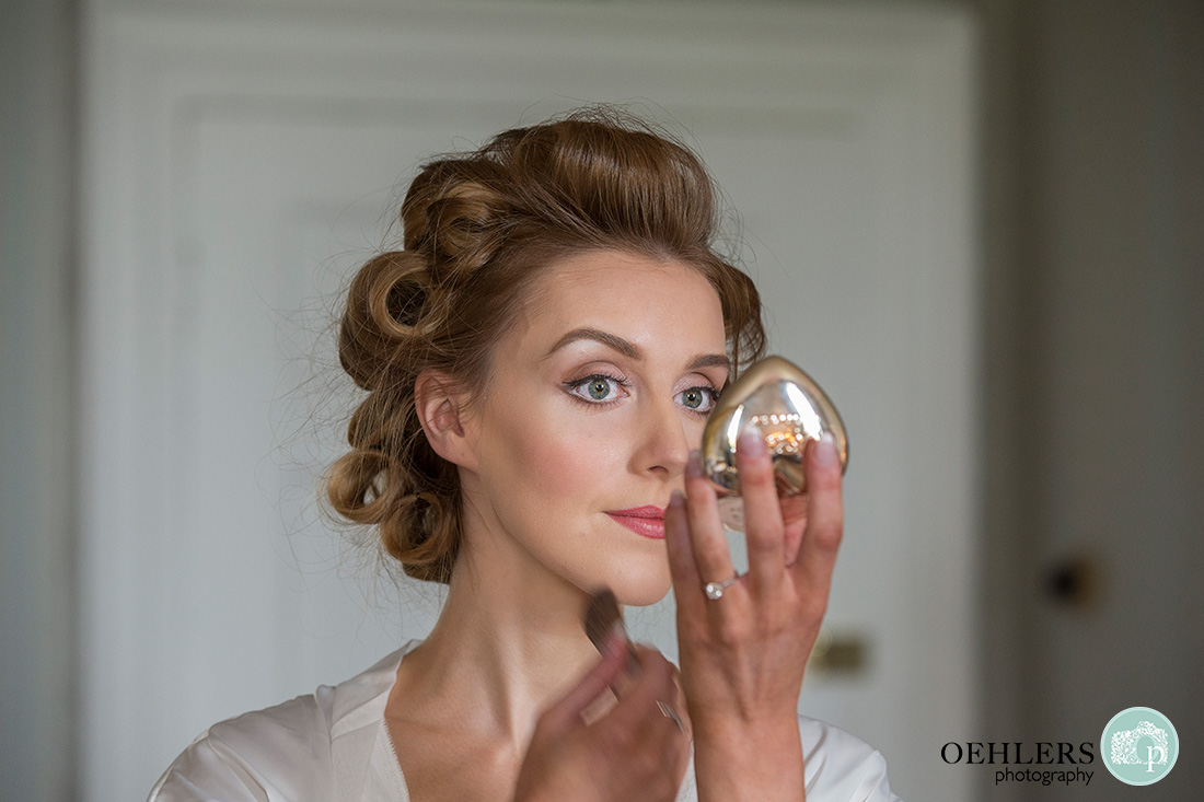 wedding photography at Norwood Park - bride putting on her foundation