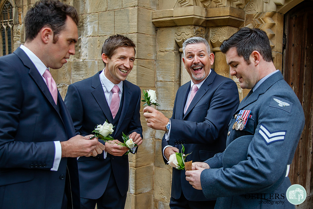 southwell minster wedding - groomsmen wondering where to place the groom's buttonhole on his uniform