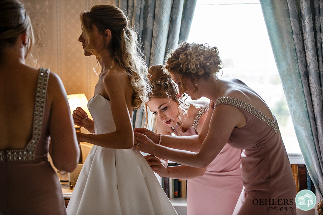 Norwood Park Wedding - bridesmaids doing up the back of the bride's dress