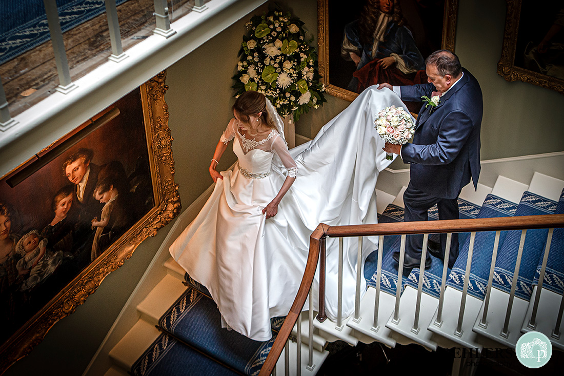 Norwood Park Wedding - dad hold the brides train as they walk down the staircase at Norwood