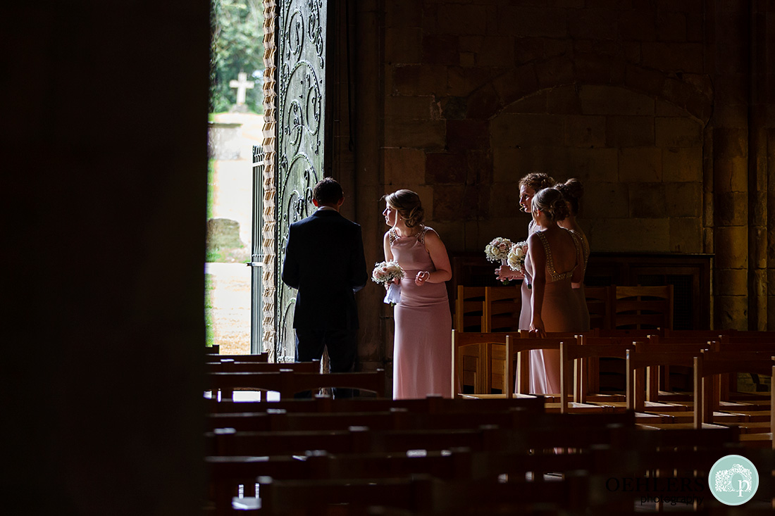Southwell Minster wedding ceremony - bridesmaid waiting for the bride with one of them looking out.