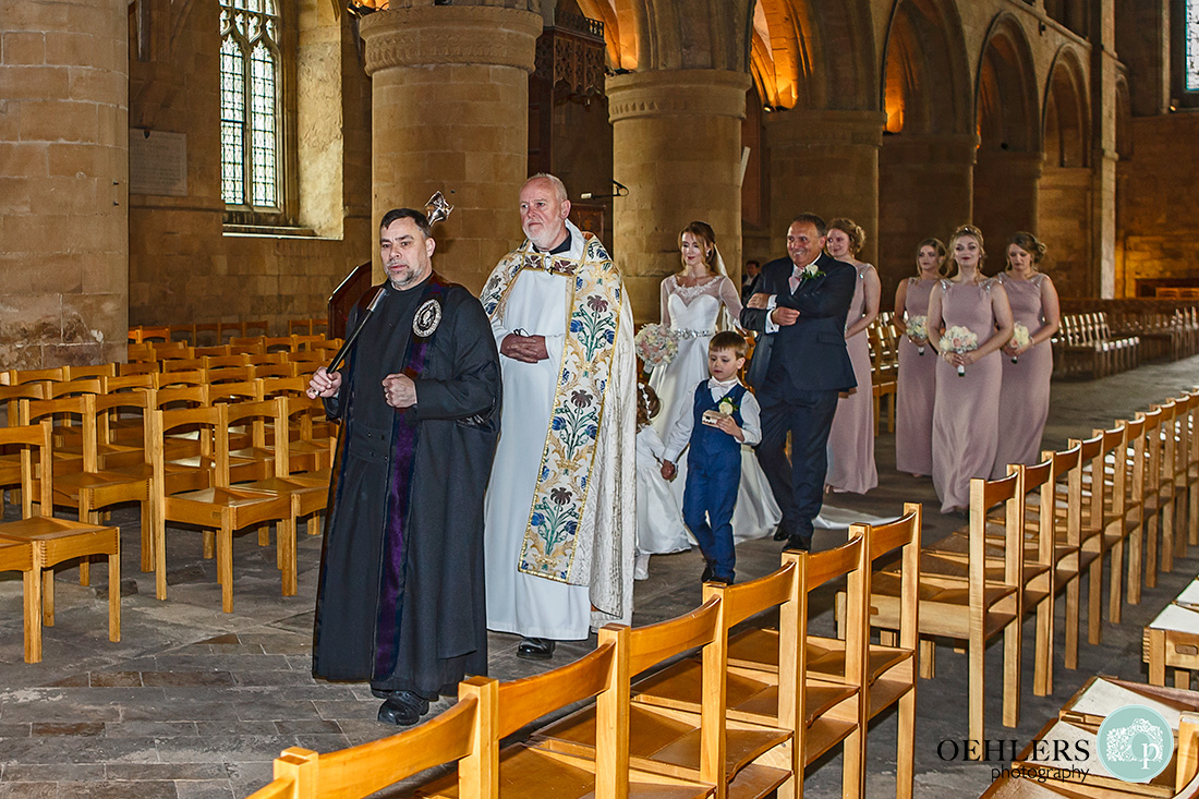 Southwell Minster wedding ceremony - the bride and bridesmaids walking down the aisle with priest.