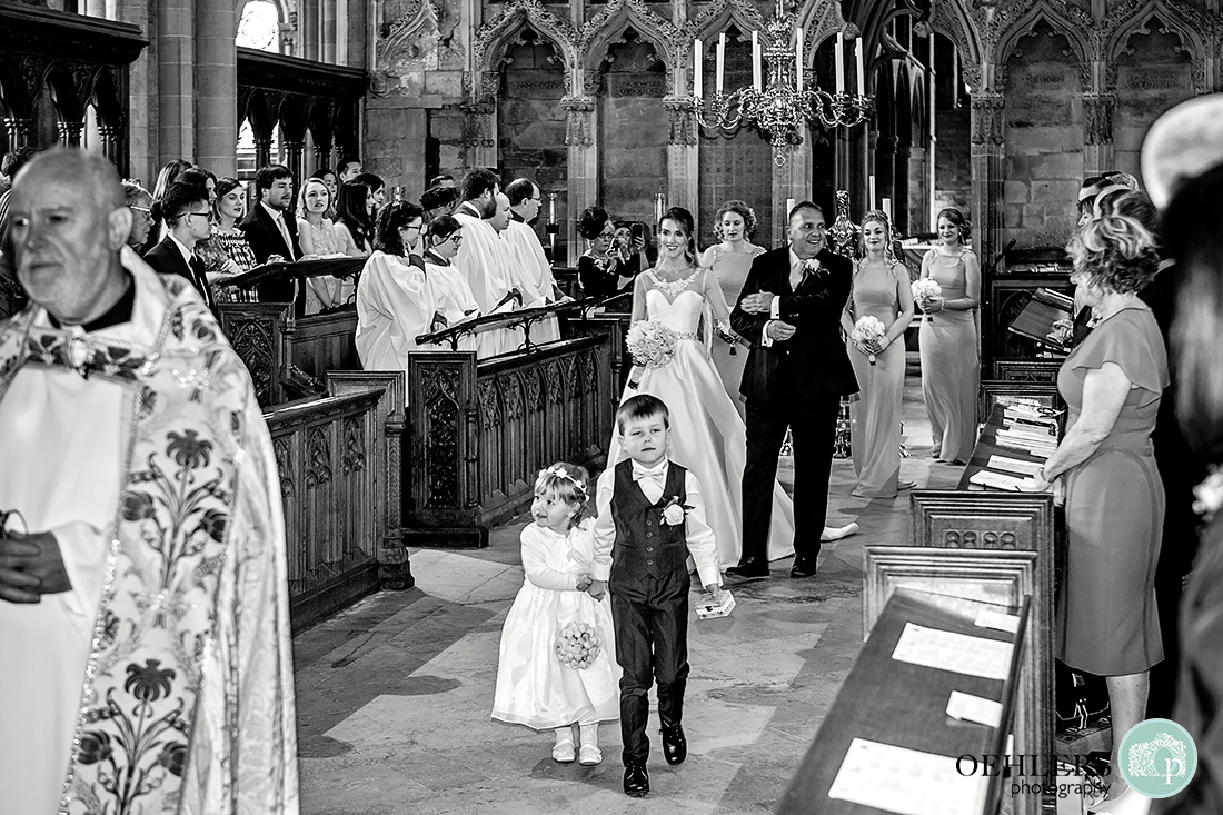 Southwell Minster wedding ceremony - bride walking down the Quire of Southwell Minster with her dad and bridal party.