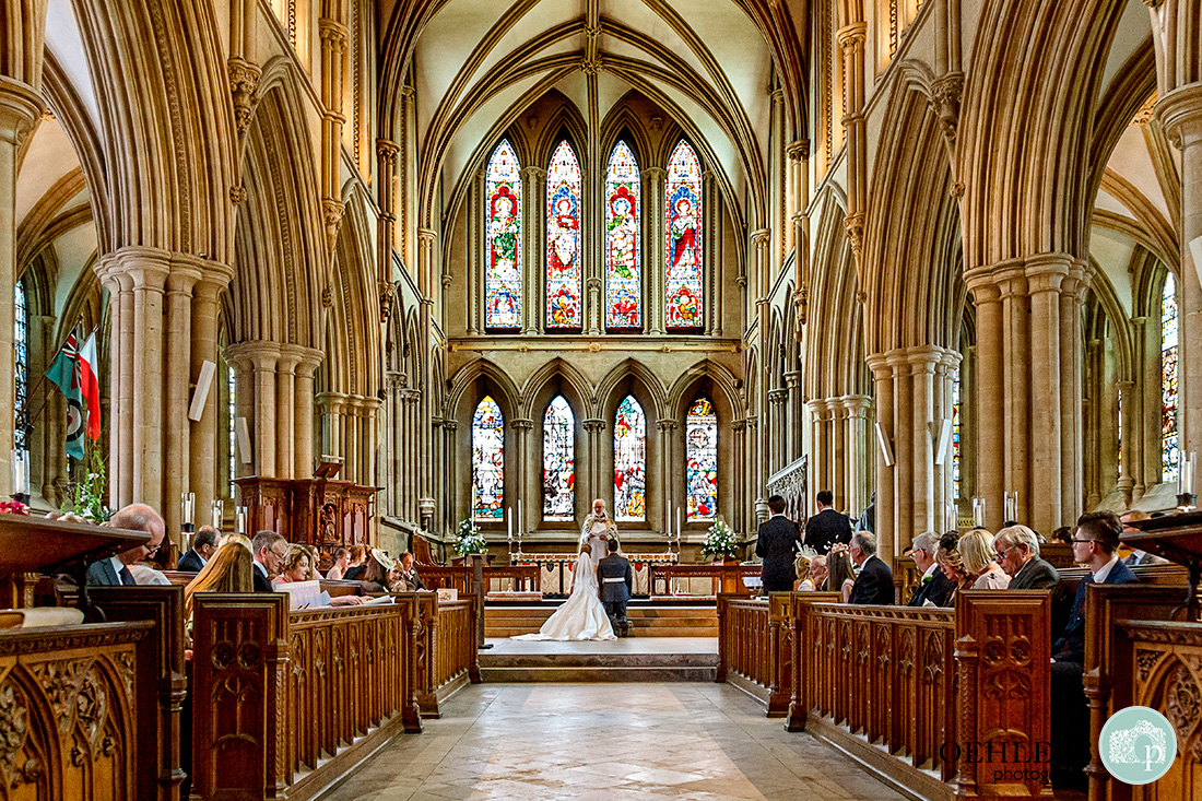 Southwell Minster wedding ceremony - looking down at the bride and groom kneeling in The Sanctuary.
