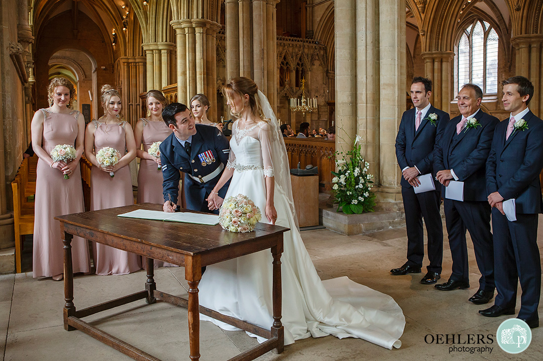 Southwell Minster wedding ceremony - signind the register with bridesmaids and groomsmen looking on