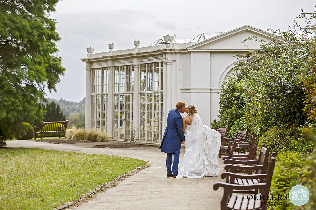 bride and groom kissing as they walk towards the camellia house at wollaton hall