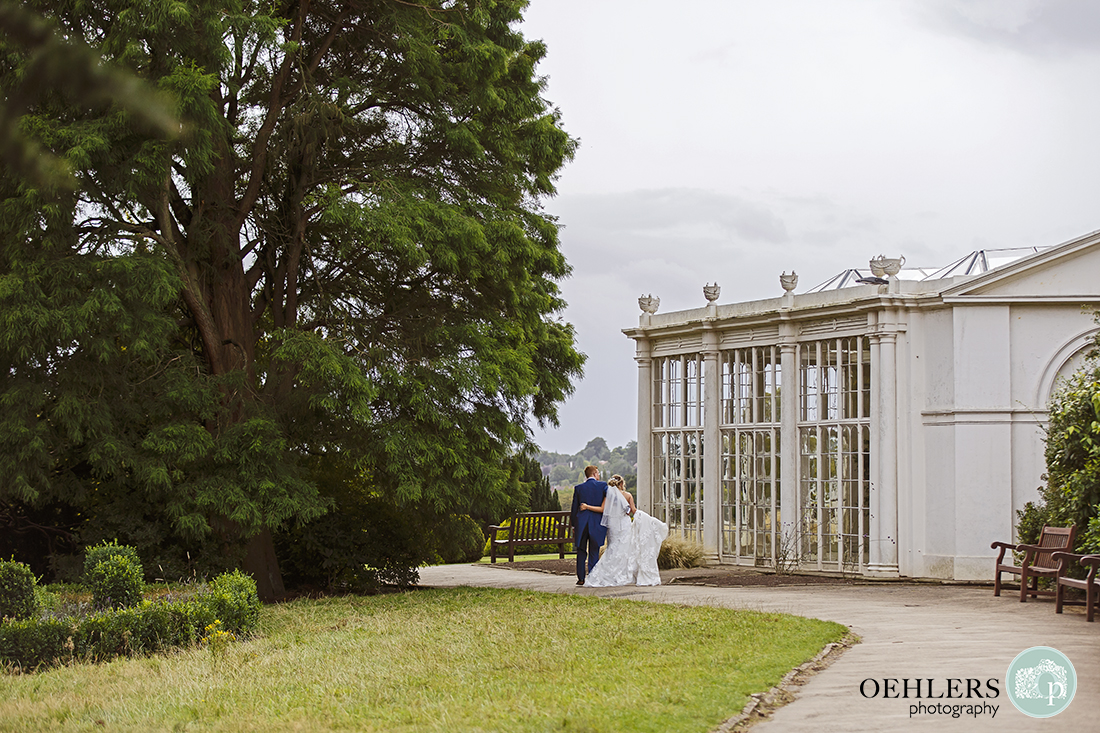 bride and groom in the distance looking into the Camillia House at Wollaton Hall