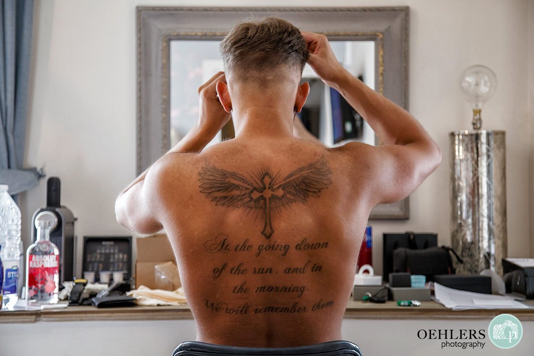 Osmaston Park wedding photography - Groom with quote written on his back whilst looking into a mirror.