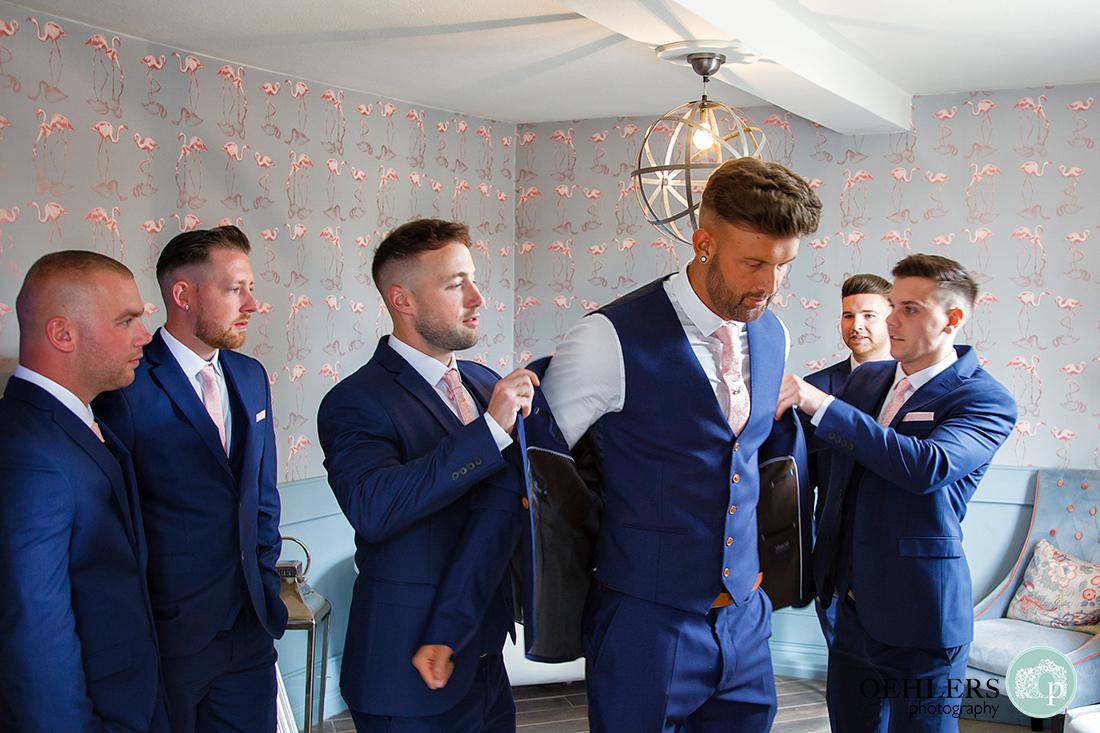 Osmaston Park wedding photography - Groomsmen helping the groom put on his jacket.
