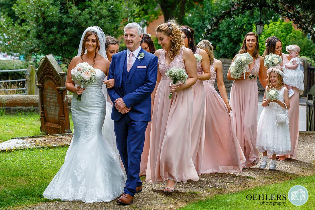 Osmaston Park wedding photography - St Martin's Church, Osmaston - Bride walking down pathway with dad and bridesmaids towards the church.