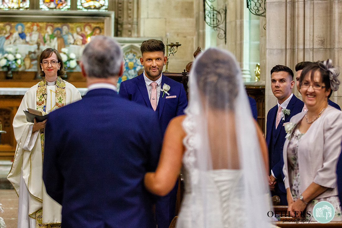 Osmaston Park wedding photography - Groom looking back at his wife to be as she and dad walks down the aisle.