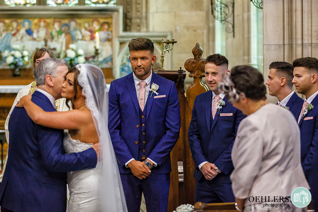Osmaston Park wedding photography - Groom looks on as the bride kisses her dad as he hands her over to the groom.
