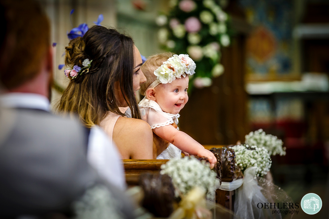 Osmaston Park wedding photography - St Martin's Church, Osmaston - a happy toddler looking at someone from a pew.