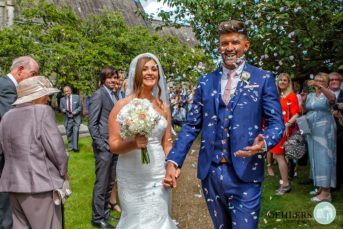 Osmaston Park wedding photography - a confetti drenched, happy couple at the end of the confetti line up.