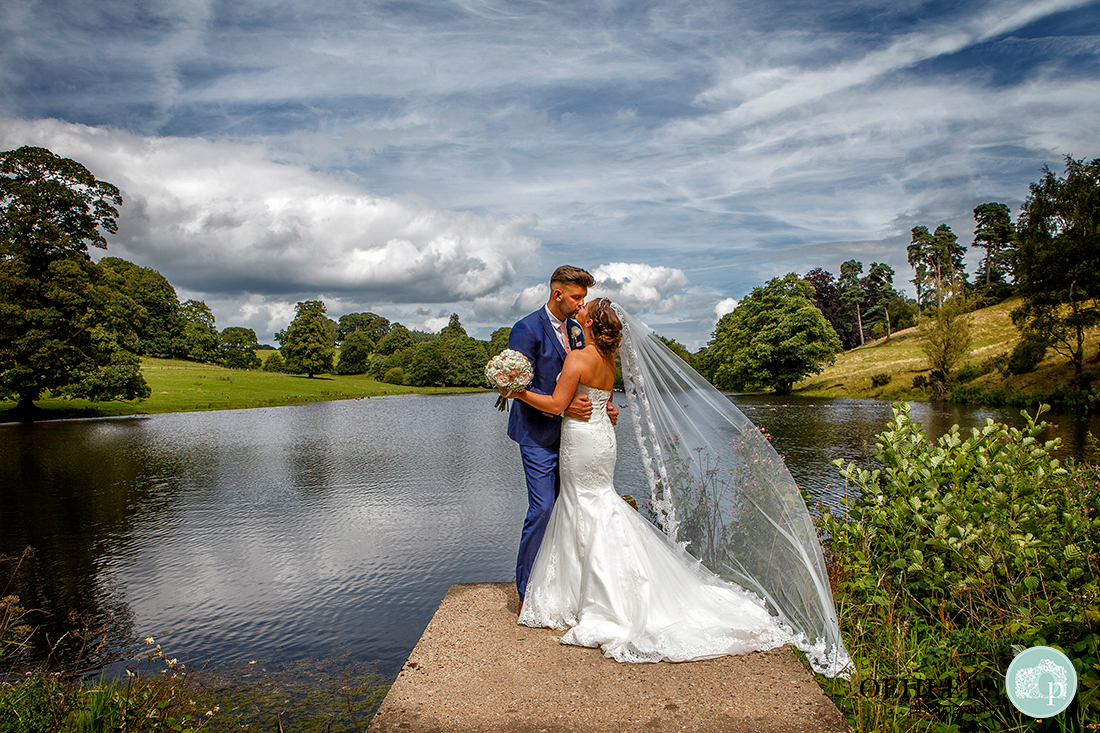 Osmaston Park wedding photography - beautiful photograph of the bride and groom in front of a lake and countryside