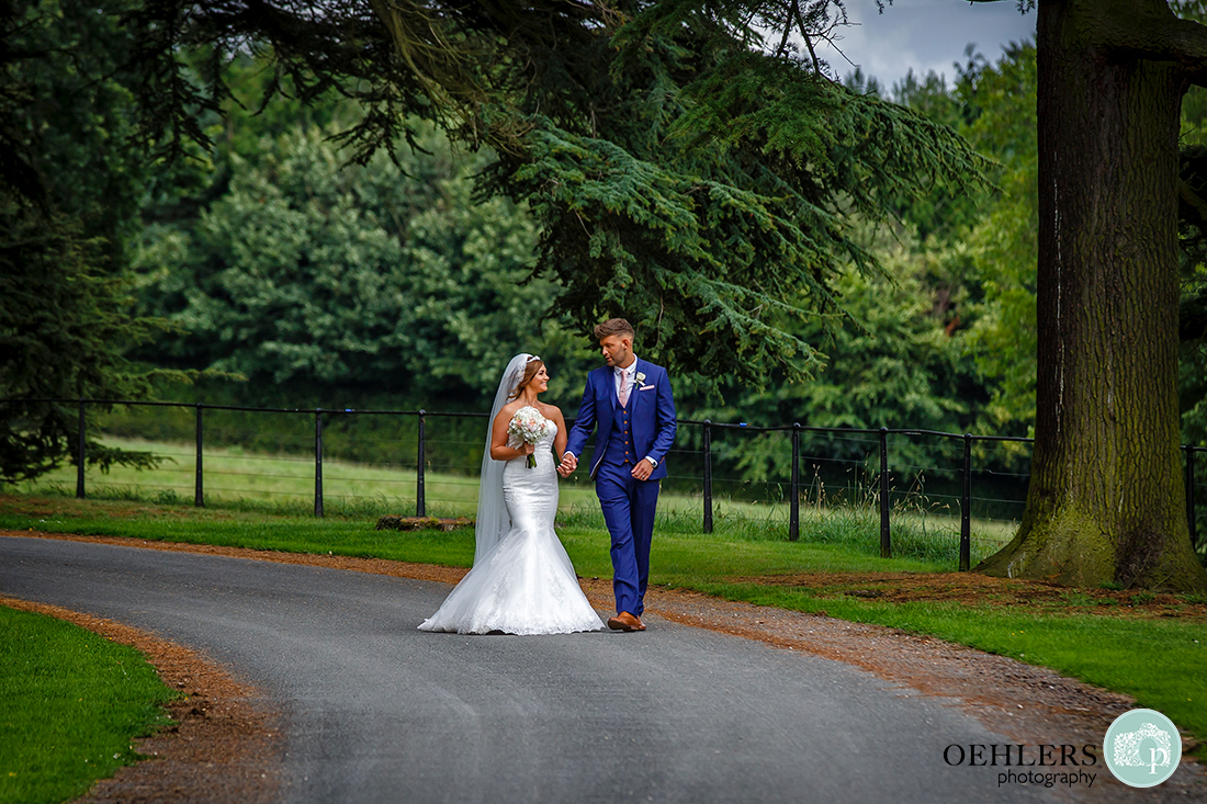 Osmaston Park wedding photography - couple walking towards the venue