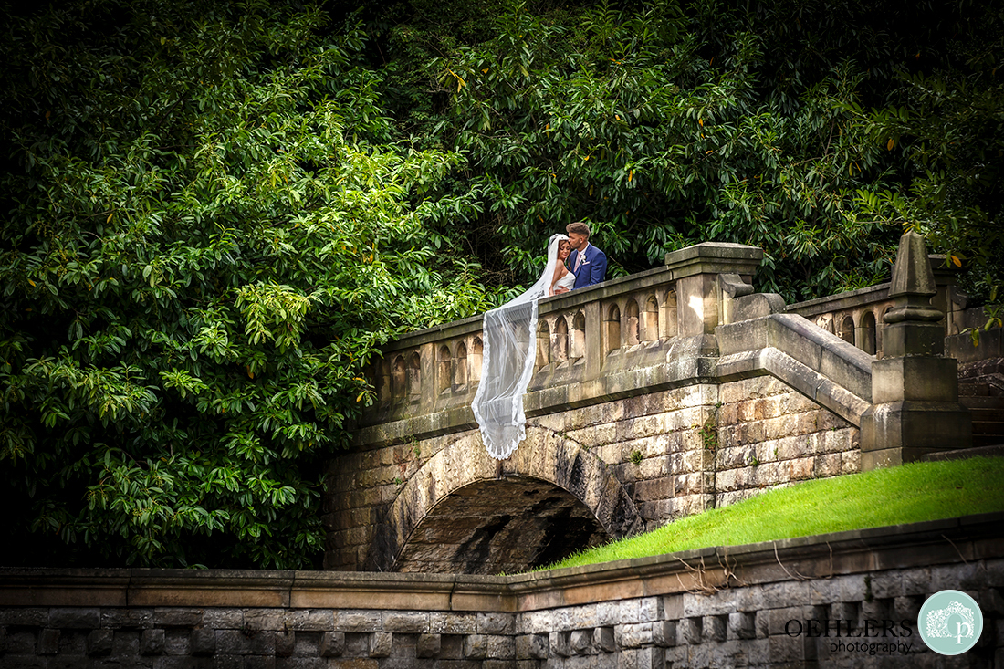 Osmaston Park wedding photography - couple on the brides with bride's veil draped over the side