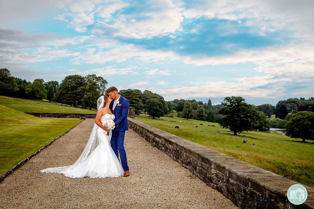 couple kissing with views of the countryside behind them