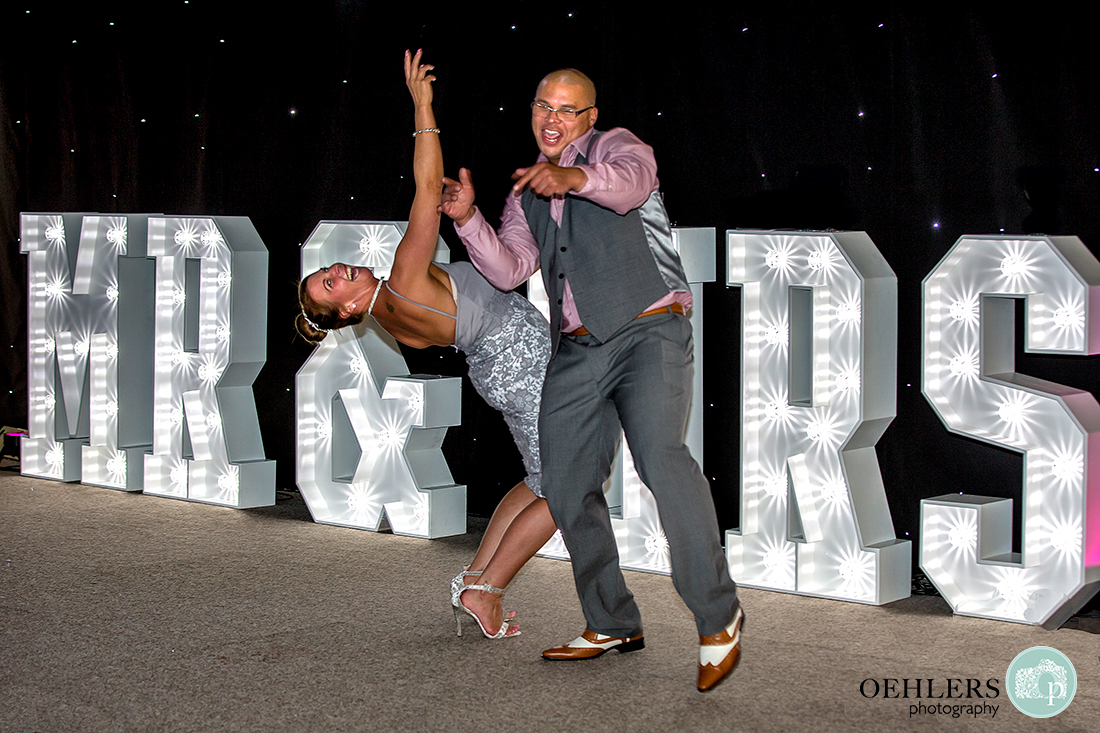 Osmaston Park wedding photography - a couple of guests dancing in front of the Mr and Mrs light stand