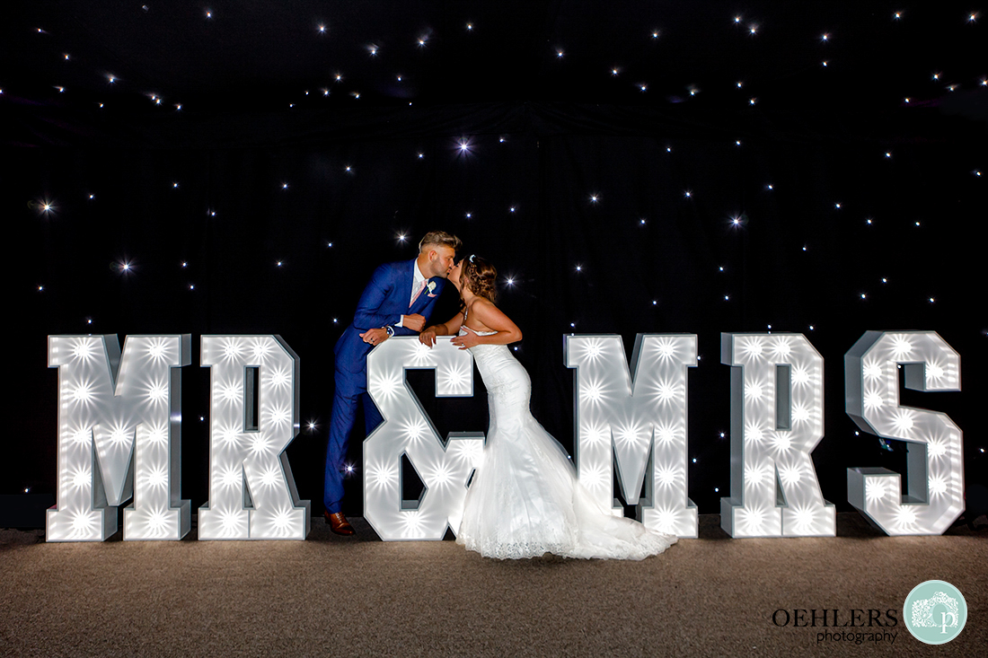 Bride and groom kissing in front of the Mr and Mrs light stand
